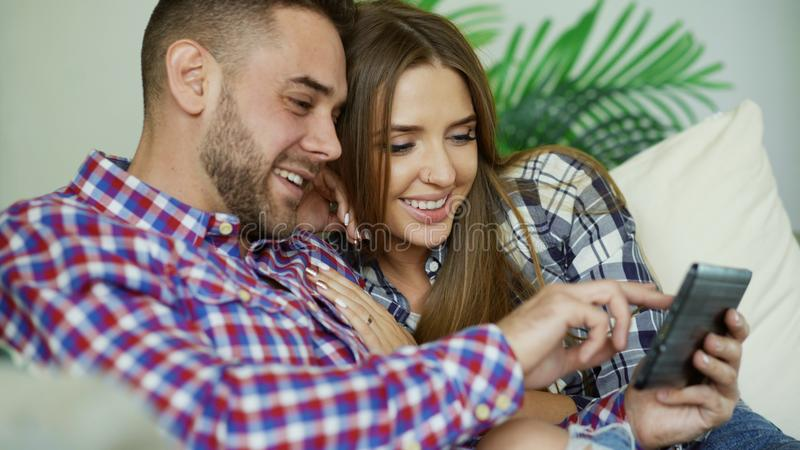 Closeup of young smiling couple using tablet computer for surfing internet and chatting sit on couch in living room at. Young attractive couple using tablet stock images