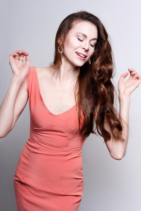 Young attractive dancing woman in coral dress stock image