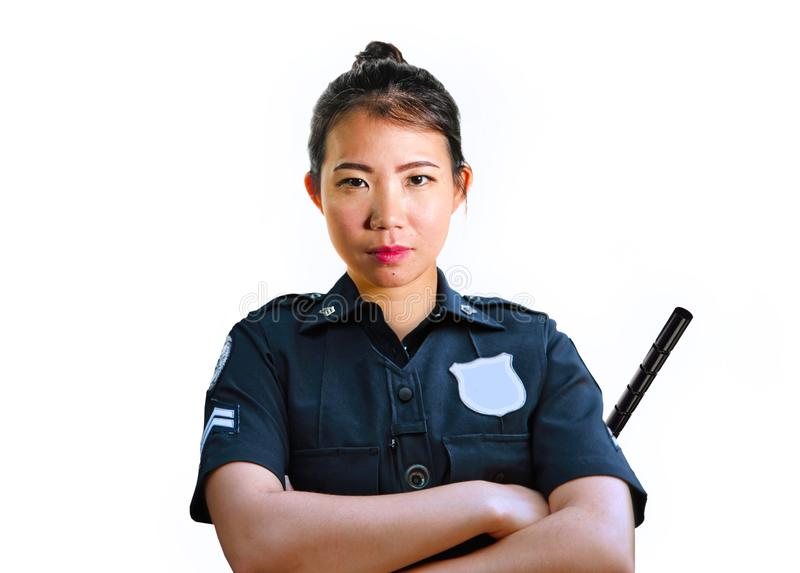 Young attractive and defiant Asian Chinese police officer in uniform holding defense stick serious isolated on white background in stock photography
