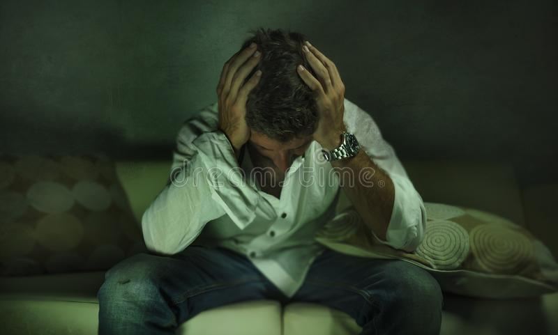 Young attractive depressed and sad shady man at home couch crying lost in pain and despair suffering anxiety crisis and depression royalty free stock images