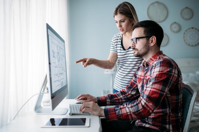 Young attractive designers working on project together royalty free stock photography