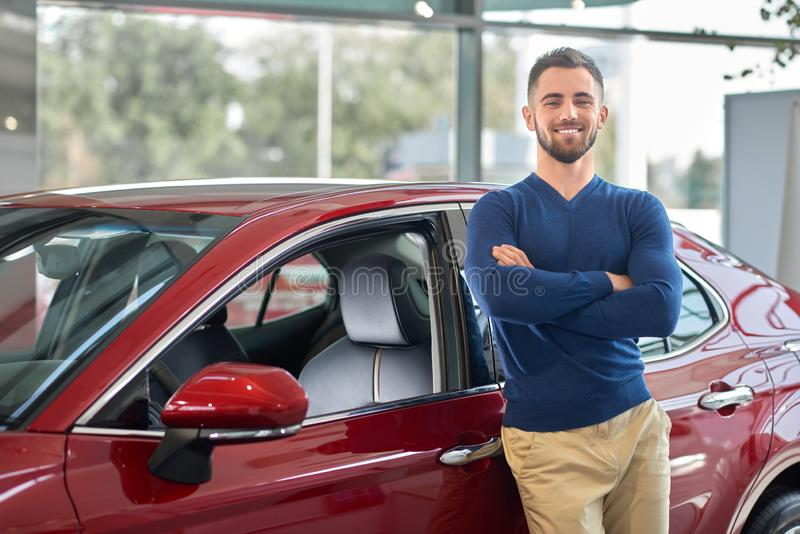 Young attractive driver smiling near his new vehicle. Happy customer in casual clothes leaning on red auto with crossing hands on breast. Brunette man with royalty free stock photography