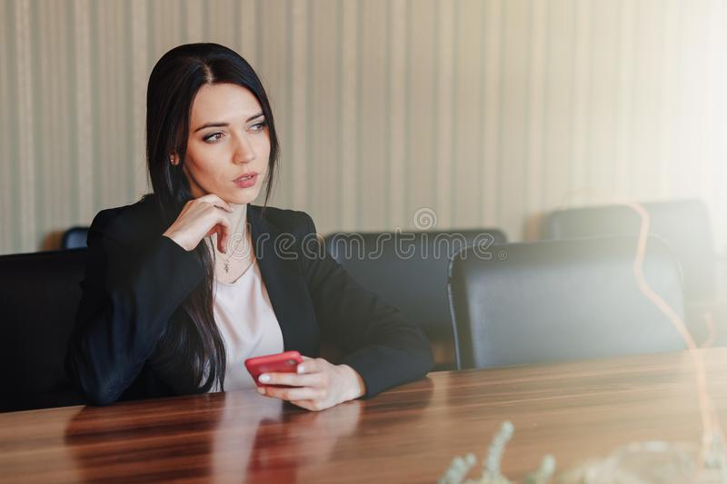 Young attractive emotional girl in business style clothes sitting at desk with phone in office or audience royalty free stock photos