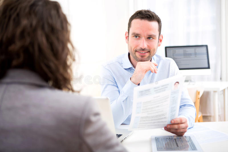 Young attractive employer analysing resume of woman stock photography