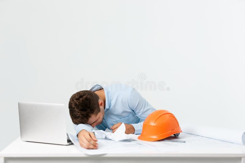 Young attractive engineer man feeling tired at work place stock photos