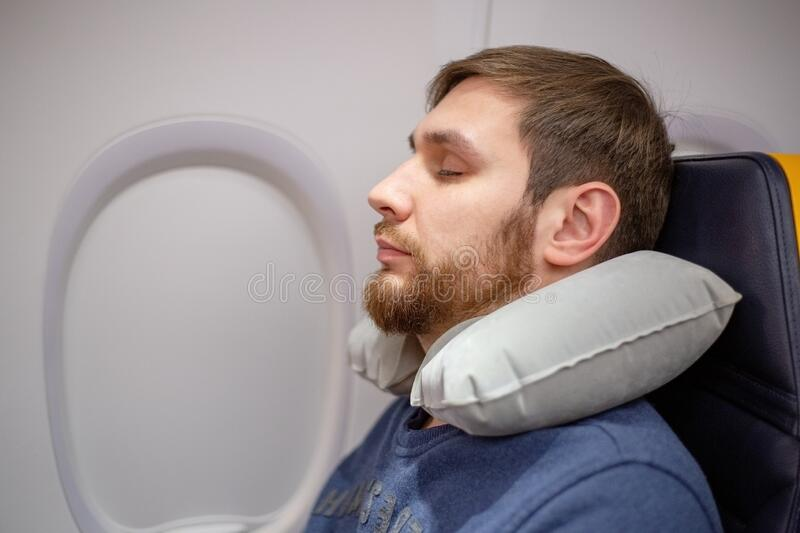 Young attractive European man 30 years with a beard sleeping, resting using inflatable neck pillow in an airplane. Comfort, stress royalty free stock image