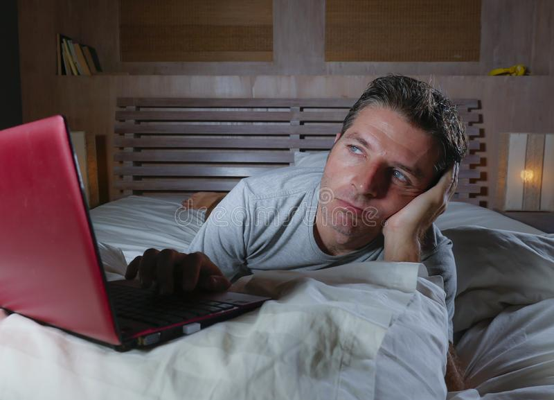 Young attractive exhausted and unhappy man upset working with laptop computer in bed late at night lying stressed and tired in bed royalty free stock photo