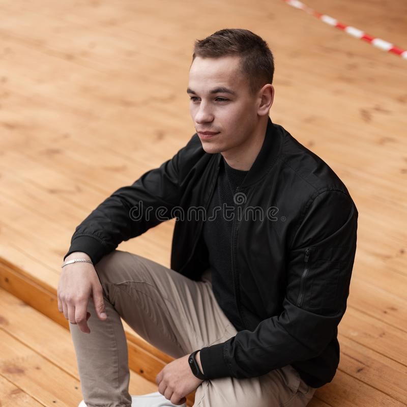 Young attractive fashionable man in a vintage stylish black jacket in beige trousers relaxes sitting on wooden steps outdoors. In the city. Modern American guy royalty free stock photos