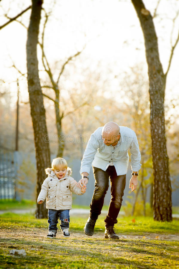 Young attractive father and little cute son playing in the park stock photos