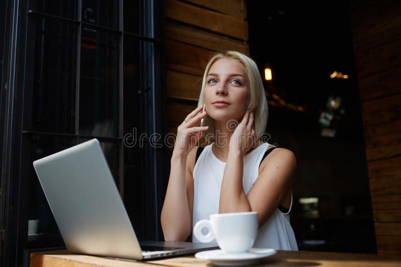 Young attractive female calling with her smart phone while sitting with portable net-book in coffee shop,. Beautiful blonde female talking on cell telephone stock photo