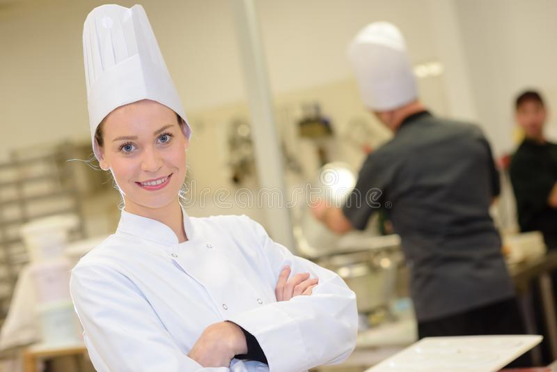 Young attractive female chef or cook in industrial kitchen stock images