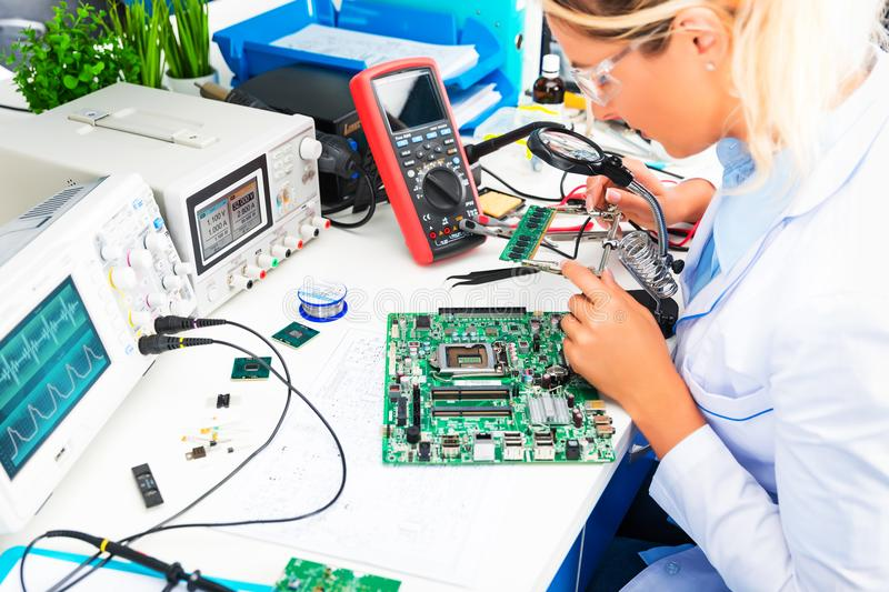 Female electronic engineer checking circuit board in laboratory. Young attractive female digital electronic engineer checking green circuit board PCB in royalty free stock photos