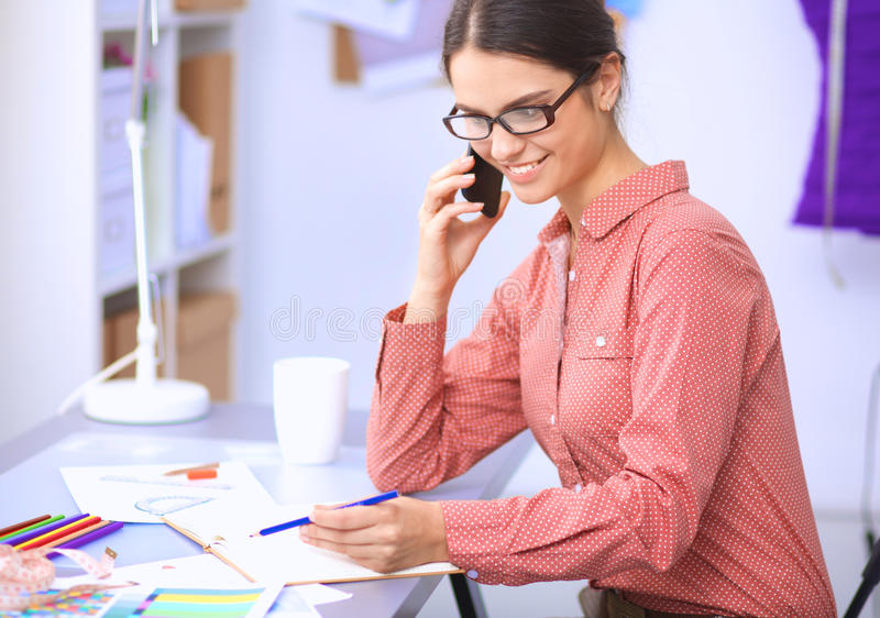 Young attractive female fashion designer working at office desk, drawing while talking on mobile royalty free stock photo