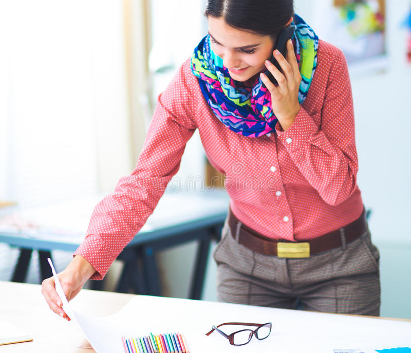 Young attractive female fashion designer working at office desk, drawing while talking on mobile royalty free stock photography