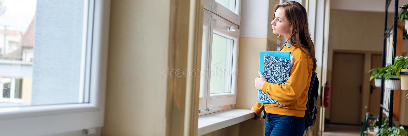 Young attractive female high school student standing by the window in the hallway at her school alone. stock photo