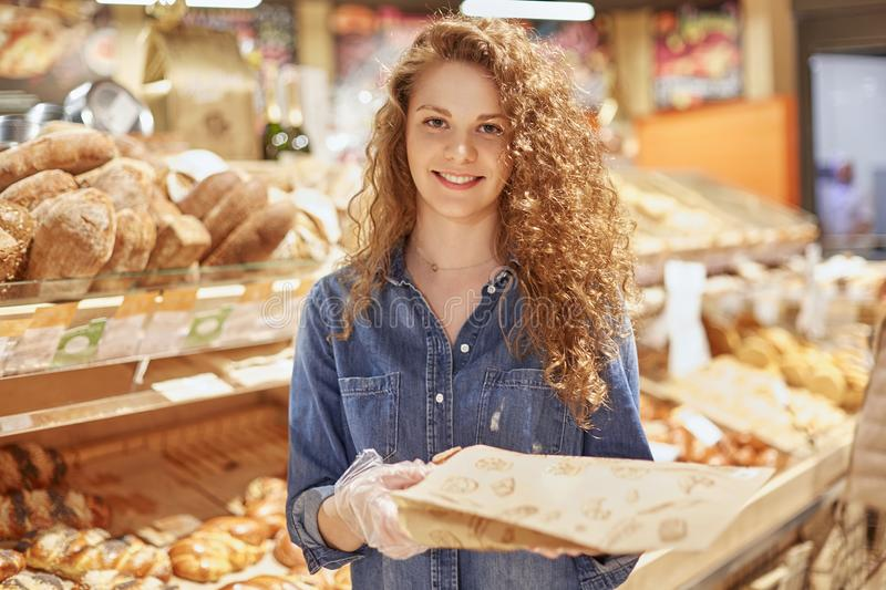 Young attractive female model with appealing appearance stands in bakery department, chooses bread or buns, spends free time in gr royalty free stock photos