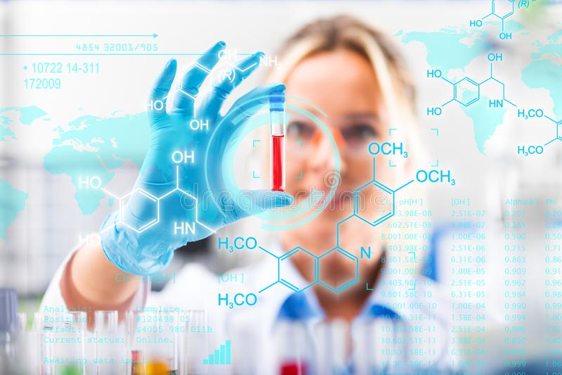 Young attractive female scientist examining test tube with substance probe royalty free stock photos