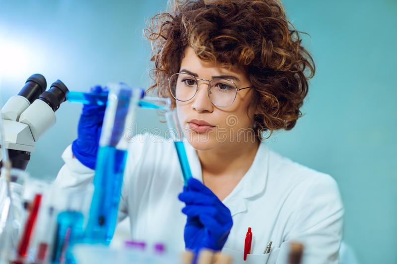 Young attractive female scientist in eyeglasses. Young attractive female scientist in protective eyeglasses and gloves using test tube with blue liquid sample stock image