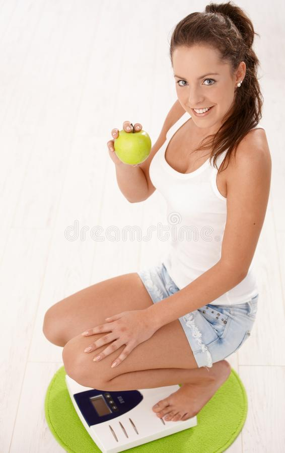 Download Young Attractive Female Squatting On Scale Smiling Stock Photo - Image: 17097796