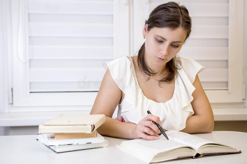 Young attractive female student with books is preparing for exams at university. Learn lessons. Education at home. Schoolgirl reading books at University of royalty free stock photos