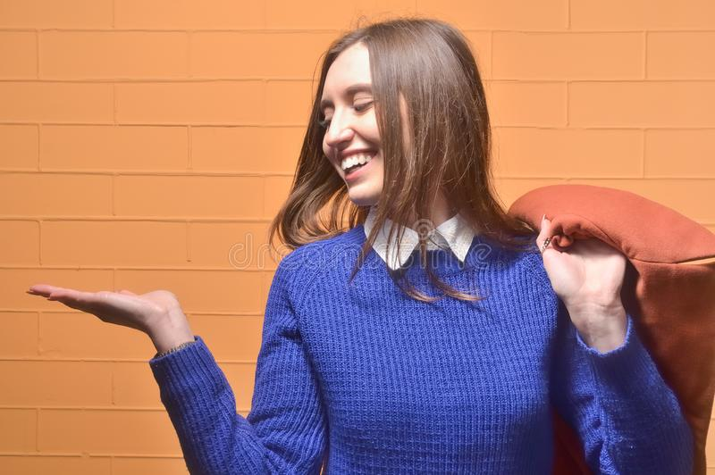 Young attractive female student dressed in a blue sweater holding a flattened palm. He looks at his hand, standing near a brick wall orange royalty free stock image