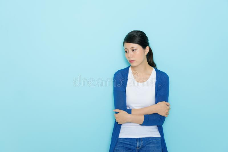 Young attractive female student getting lovelorn. Feeling sadness looking at empty area and hands crossed standing in blue background royalty free stock photo