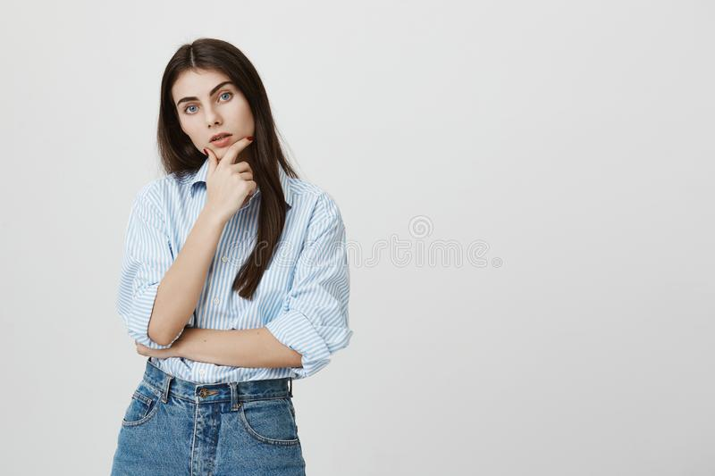 Young attractive female student looking intrigued at camera, thinking about something while touching chin with hand and. Standing over gray background. Woman in stock photo