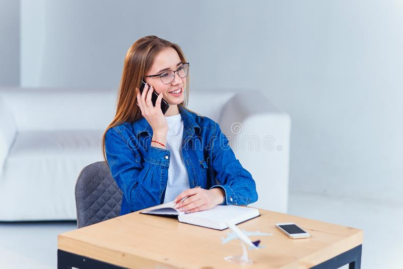 Young attractive female student uses smartphone while studying at home. Young attractive female student speaks by smartphone while studying at home. She sits at stock image