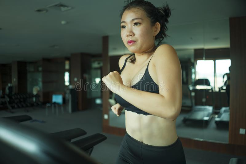 Young attractive and fit Asian Chinese woman doing running workout at hotel gym or fitness club jogging in treadmill training hard. In healthy lifestyle and royalty free stock image