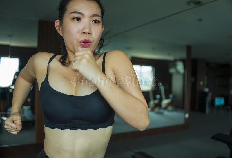 Young attractive and fit Asian Chinese woman doing running workout at hotel gym or fitness club jogging in treadmill training hard. In healthy lifestyle and stock photo
