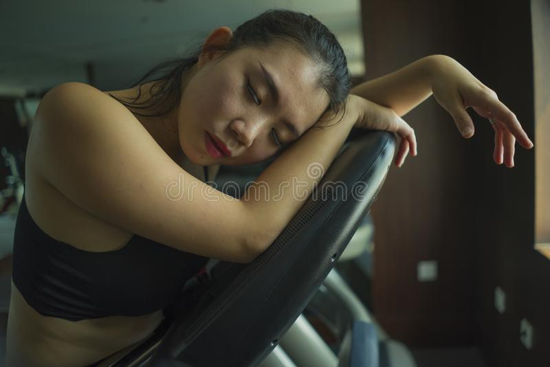 Young attractive and fit Asian Japanese woman exhausted during running workout at hotel gym or fitness club jogging in treadmill. Training hard with tired face royalty free stock photography