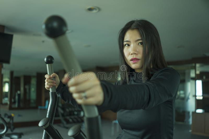 Young attractive and fit Asian Korean woman doing running workout at hotel gym or fitness club jogging in treadmill training hard. In healthy lifestyle and body stock photos