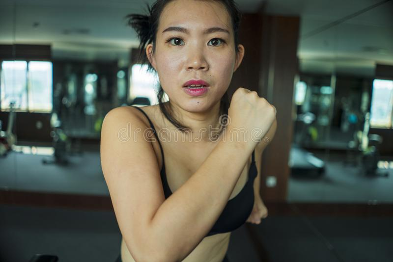 Young attractive and fit Asian Korean woman doing running workout at hotel gym or fitness club jogging in treadmill training hard. In healthy lifestyle and body royalty free stock image