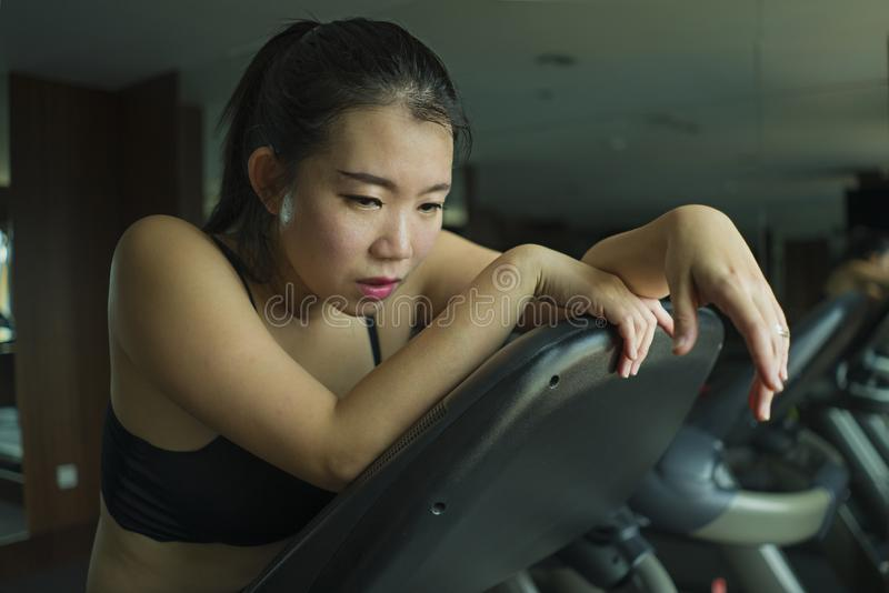 Young attractive and fit Asian Korean woman exhausted during running workout at hotel gym or fitness club jogging in treadmill. Training hard with tired face stock photography