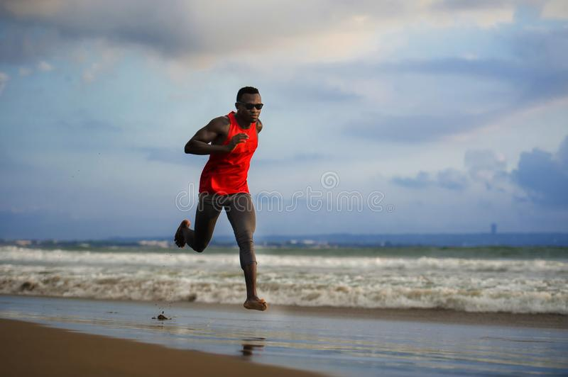 Young attractive fit athletic and strong black afro American man running at the beach training hard and sprinting on sea water in stock photos