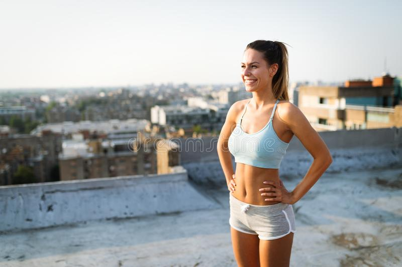Young attractive fit sporty woman doing workout on the rooftop on sunny day stock image