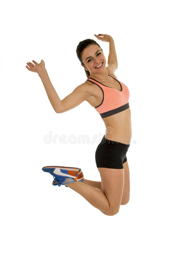 Young attractive fitness trainer woman jumping high excited and happy. Wearing clothes isolated on white background in healthy lifestyle and body energy concept stock image