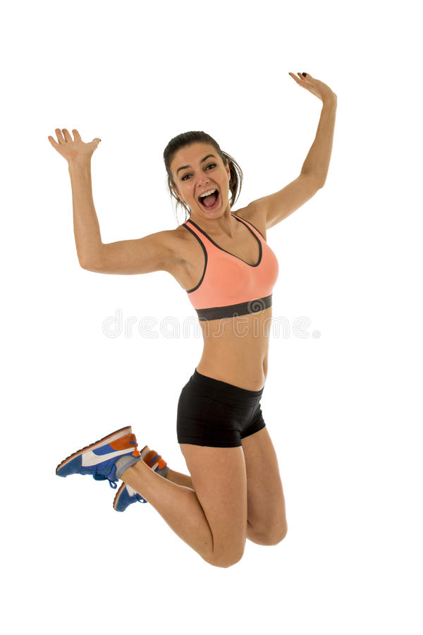Young attractive fitness trainer woman jumping high excited and happy stock photography