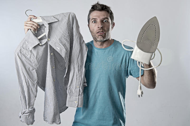 Young attractive and frustrated man holding iron and shirt stressed and tired in bored and lazy face. Expression in male ironing going wrong and domestic work royalty free stock photography