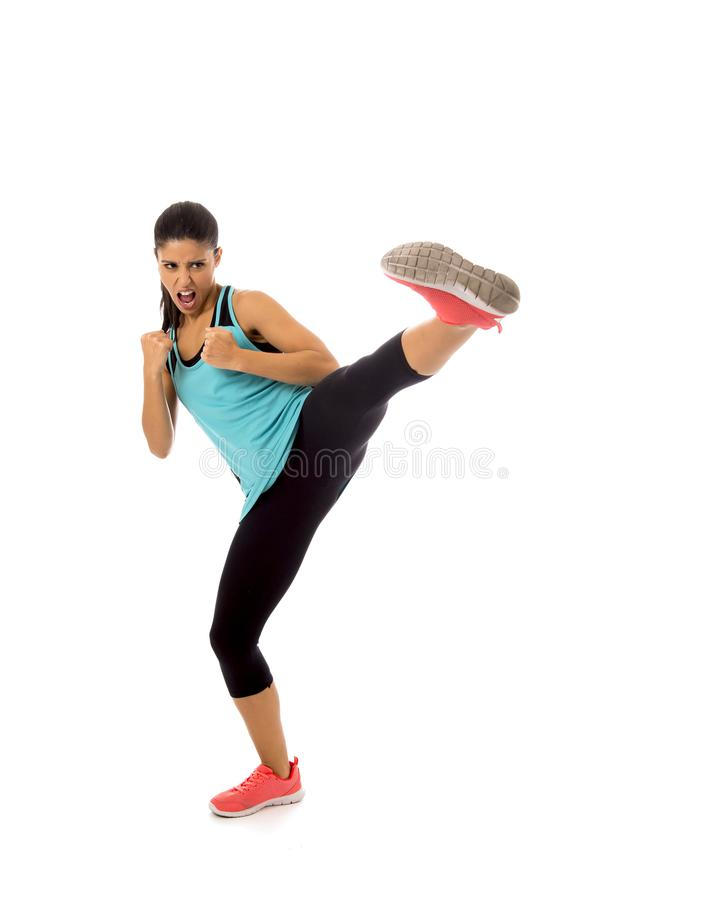 Young attractive and furious latin sport woman in fight and kick boxing training workout throwing aggressive kick attack royalty free stock photos