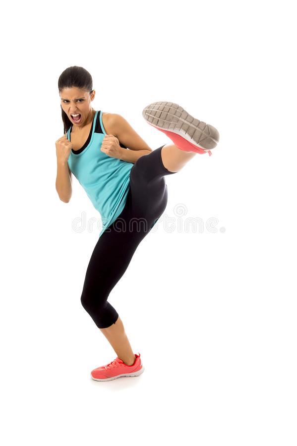 Young attractive and furious latin sport woman in fight and kick boxing training workout throwing aggressive kick attack. Isolated on white background in gym stock photos