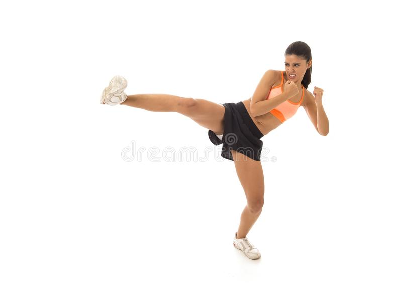 Young attractive and furious latin sport woman in fight and kick boxing training workout throwing aggressive kick attack stock photos