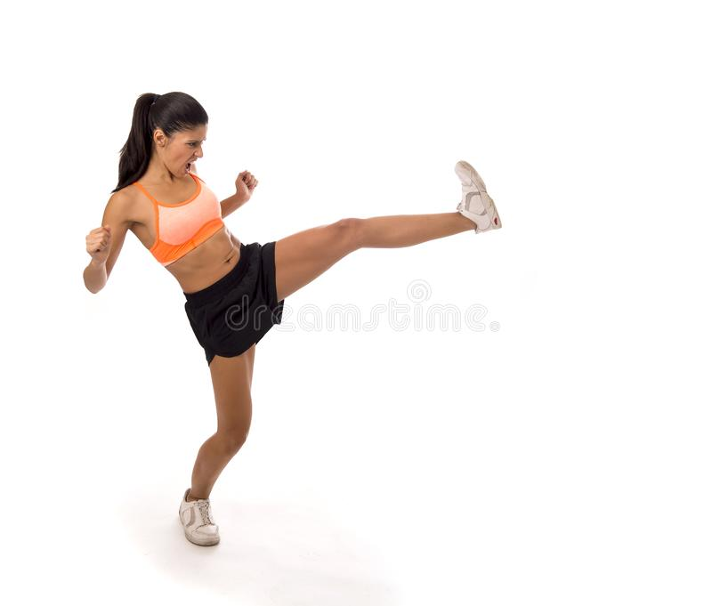 Young attractive and furious latin sport woman in fight and kick boxing training workout throwing aggressive kick attack royalty free stock photo