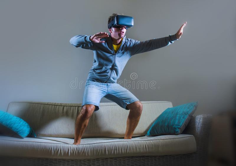 Young attractive gamer man using VR goggles headgear technology playing simulator 3D video game having fun on home sofa couch enjo. Young attractive gamer man stock images