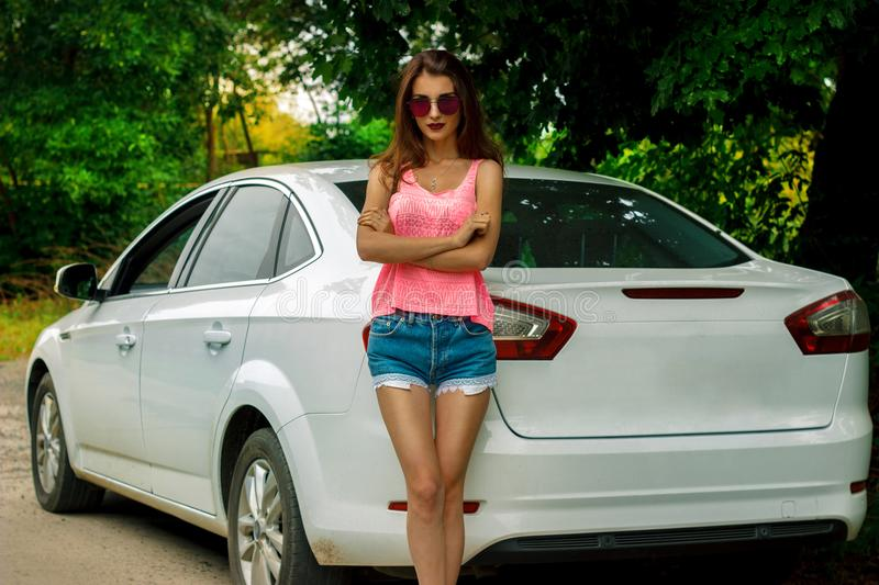 Attractive girl in a bright dress posing near the white car stock photos