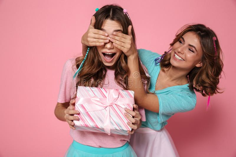Young attractive girl in colorful tshirt surprises her friend while giving present stock photography