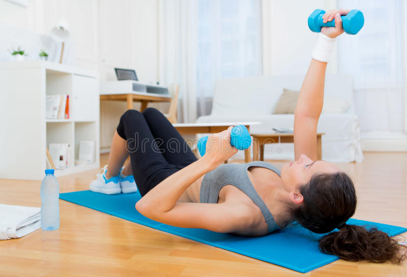Young attractive girl doing exercise at home royalty free stock photo