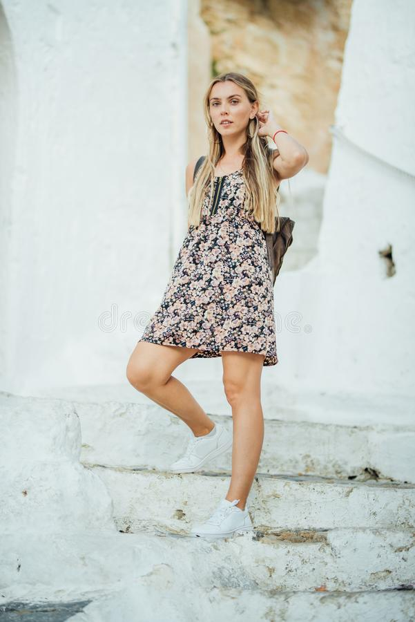 Young attractive girl in flower dress posing on white stairs in Lindos city, Greece stock photo