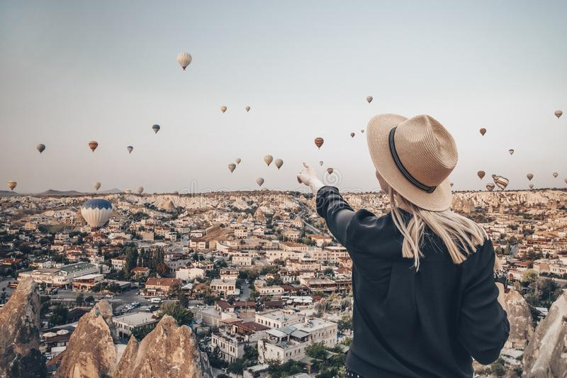 Young attractive girl in a hat stands on the mountain with flying air balloons on the background. Finger pointing girl stock photos