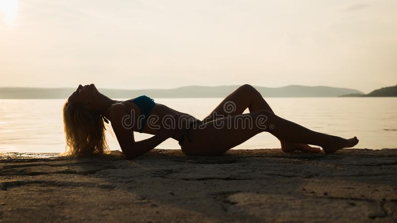 Young attractive girl model silhouette on the beach stock photography